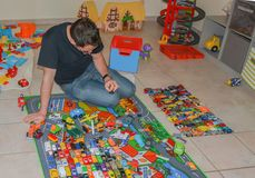 Fadern spelar med modeller för barn` s av bilar Arkivfoton