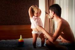 fadern spelar med och talar till den blonda dottern på soffan Arkivbild