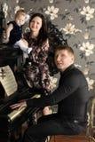 Fadern spelar pianot, och modern med gulligt behandla som ett barn royaltyfria bilder