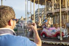 Fadern tar foto eller video av hans dotter på karusellen på telefonen arkivfoton