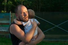 Fadern tröstar den lilla sonen arkivfoto