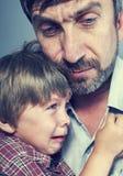 Fadern tycker synd om hans son Fotografering för Bildbyråer
