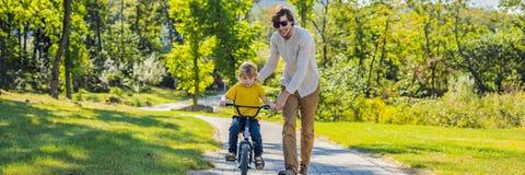 Fadern undervisar hans sonritt ett cykelBANER, LÅNGT FORMAT arkivbild
