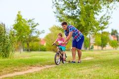 Fadern undervisar sonen att rida cykeln arkivfoton