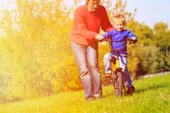 Fadern undervisar sonen att rida cykeln utomhus Arkivfoto
