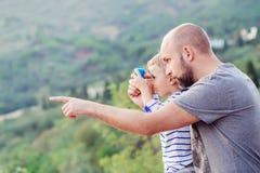 Fadern visar hans son något i avståndet Arkivfoton