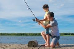 Fadern visar hans son på pir hur man rymmer en metspö för att fånga fisken, mot ett härligt landskap royaltyfria foton