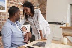 Fadern Working On Laptop rymmer den nyfödda sonen med modern arkivbild