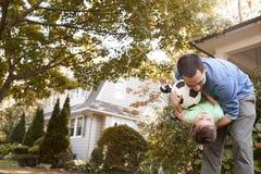 FaderPlaying With Soccer boll i trädgård med sonen arkivbilder