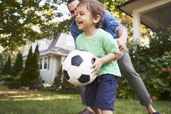 FaderPlaying Soccer In trädgård med sonen royaltyfri fotografi