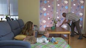 Faderrengöringgolvet med dammsugaren och mamman spelar med behandla som ett barn soffan 4K arkivfilmer