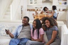 FaderSitting On Sofa Watching TV med tonårs- döttrar arkivfoton