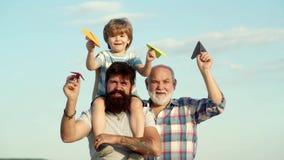 Faderson och farfar som spelar - familjtid tillsammans Utveckling för tre män Ungepilot med leksakjetpack mot himmel lager videofilmer
