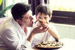 Faderson som äter en italiensk pizza Royaltyfri Fotografi