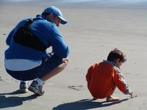 Faderundervisning hans son som ska skrivas Royaltyfria Bilder
