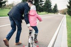 Faderundervisningdotter som rider cykeln arkivfoto
