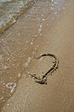 Fading Love. Heart drwan in the sand of a beach, while the waves fade it away Stock Images