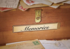 Fading Memories. A simple, old wooden box with a brass latch and label holder containing the word, memories. Old letters and postcards are piled up in front and stock image