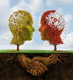 Fading Team. Business concept with two autumn trees losing leaves in the shape of human heads with roots underground shaped as shaking hands as a team agreement Stock Images