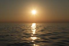 Fadingu słońce nad wodą Fotografia Stock
