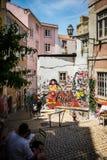 Fadografitti i gränd i Lissabon Portugal med en gentleman som sitter i skuggan arkivfoto