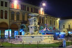 Decorated town for the New Year. There is a merry-go-round behind the beautiful medieval fountain Stock Photos