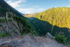 Fagaras mountain ridge in the morning. Rocky formations in sunlight. beautiful summer scenery. cascada balea in the valley royalty free stock photos
