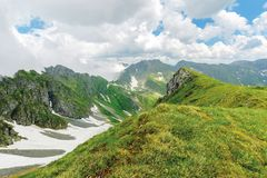 Fagaras mountain ridge in summer. Spots of snow on grass of steep slope. rocky tops. cloudy weather. romania landscape stock photos