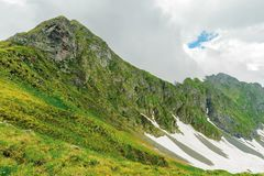 Fagaras mountain ridge in summer. Spots of snow on grass of steep slope. rocky tops. cloudy weather. romania landscape stock photo