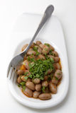 Fagioli cucinati sul piatto bianco con la forcella - dispositivi d'avviamento turchi Immagini Stock