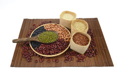 Fagioli dei cereali e dei chicchi di grano utili per salute in cucchiai di legno su fondo bianco Immagini Stock