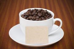 Fagioli della tazza di caffè sulla tabella di legno con la scheda Immagini Stock