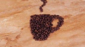 Fagioli della tazza di caffè Sulla tavola del marmo della cucina un segno dei fagioli di una tazza di caffè video d archivio