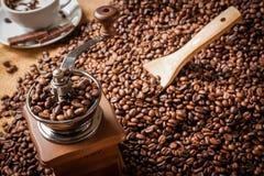 Fagioli e tazza di caffè del macinacaffè Fotografie Stock