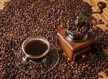 Fagioli e tazza di caffè del macinacaffè Fotografia Stock