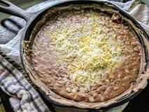 Fagioli rifritti il nero in padella del ferro con formaggio Immagini Stock