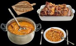 Fagioli in salsa cucinati serviti con l'arrosto di agnello ed il pane scuro isolati su fondo nero Immagine Stock