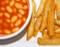 Fagioli in salsa e patatine fritte/patate fritte dorate su un piatto bianco Fotografia Stock Libera da Diritti