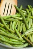 Fagioli verdi fritti ed utensili di legno Fotografia Stock