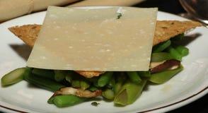 Fagiolino dell'aperitivo ed insalata dei funghi coperta dal cracker del grano e dalla fetta di parmigiano Fotografie Stock