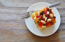 Fagiolo della guarnizione del dolce del burro ed insalata arancio della frutta secca con la forcella sul piatto fotografie stock