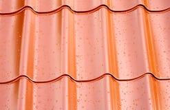 Fagment de toit rouge en métal avec beaucoup de baisses de l'eau comme fond Images libres de droits