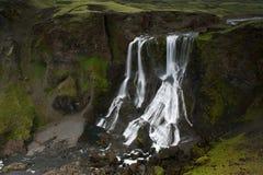 Fagrifoss (bella cascata) fra le scogliere muscose in Islanda Fotografia Stock