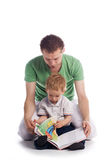 Faher with child. A father reading a book to his young baby son. Isolated on white Royalty Free Stock Image