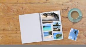 Fahne Photobook-Album auf Holztischhintergrund mit Reise-Fotos und Kaffee oder Tee in der Schale Lizenzfreies Stockfoto