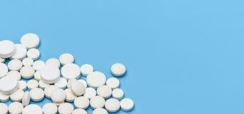 fahne Viele weißen runden Tabletten auf der Unterseite verließen auf einem blauen Hintergrund, auf dem Recht ein leerer Raum für  stockfotografie