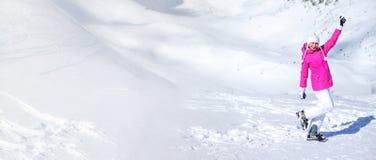 Fahne von Ski Pistes und von weißem Berg mit junger Frau im Rosa lizenzfreie stockbilder