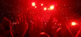 Fahnen-Hintergrund-Konzertpublikum mit roten Lichtern am Festival stockfotografie