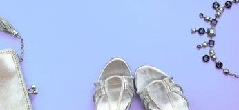 Fahnen-Satz der Mode-Accessoire-Ebene legen Schuhhandtaschenhalskettenschmuck-Silberfarbe auf purpurroten Draufsicht-Kopienraum d stockfotografie