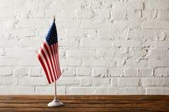 Fahnenmast Staaten von Amerika auf Holzoberfläche gegen Backsteinmauer stockbild